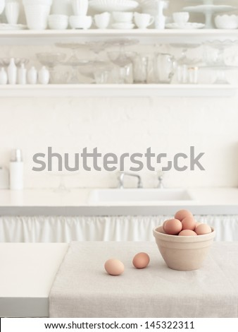 Basket of brown eggs on countertop with bowls on shelf in white kitchen - stock photo