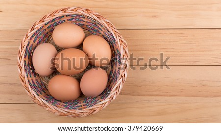 Basket of brown eggs on wood surface