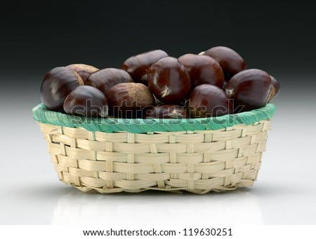 basket of chestnuts on gradient background - stock photo