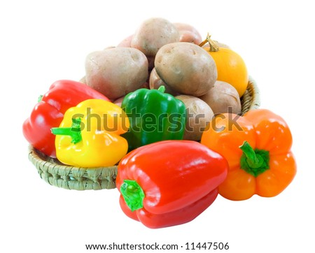 Basket of colorful capsicum, desiree potatoes and yellow squash on a white background