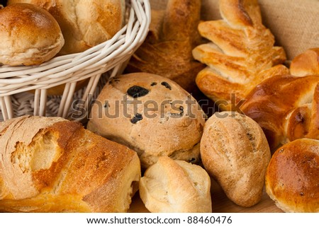 Basket of different types of gourmet bread with flour, sesame seeds and nuts - stock photo