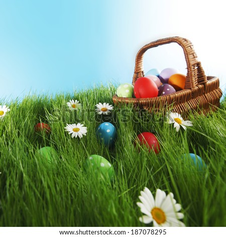 Basket of easter eggs on green grass and flowers