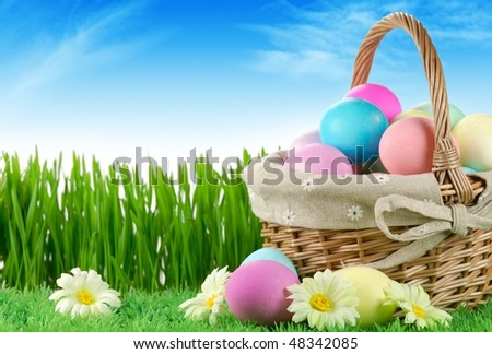Basket of easter-eggs  on meadow at sunny day. - stock photo