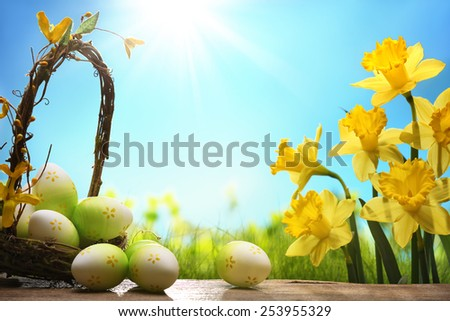 Basket of easter eggs with daffodil flower - stock photo