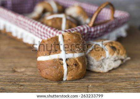 basket of easter hot cross buns on wooden background - stock photo
