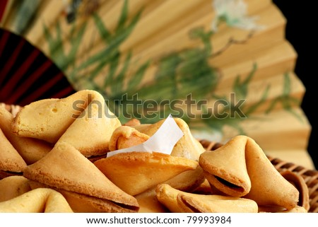 Basket of fortune cookies with oriental fan in soft focus in background.  Macro with shallow dof. - stock photo