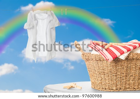 Basket of fresh laundry against blue sky with rainbow - stock photo