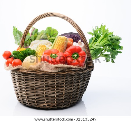 Basket of fresh raw organic vegetable produce, assortment of corn, peppers, broccoli, mushrooms, beets, cabbage, parsley, tomatoes, isolated on light background - stock photo