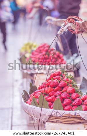 Basket of fresh strawberries sold in a street market in china. Fresh and healthy fruits with a retro instagram filter applied. - stock photo