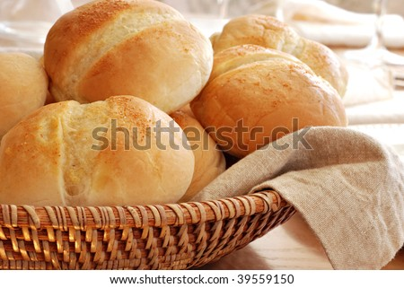 Basket of freshly baked dinner rolls with tableware in background.  Macro with shallow dof. - stock photo