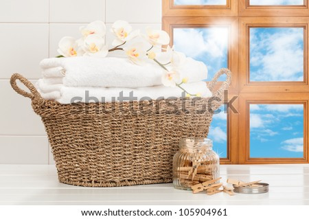 Basket of freshly laundered towels in sunlit kitchen window - stock photo