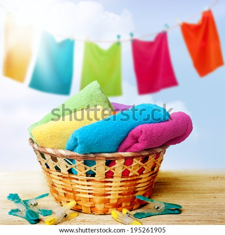 Basket of freshly laundered towels on a summer blue sky  - stock photo