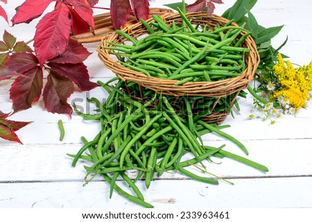 basket of green beans laid on a white wooden table - stock photo