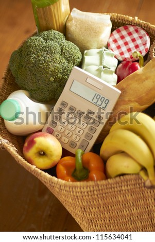 Basket Of Groceries With Calculator - stock photo
