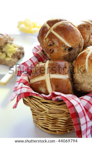 Basket of hot cross buns, with one cut and buttered in the background.  Easter symbol. - stock photo