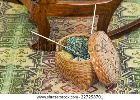 Basket of Knitting on Decorative Rug Beside Chair - stock photo