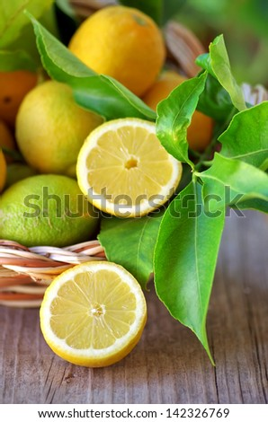 Basket of lemons and half lemons on table - stock photo