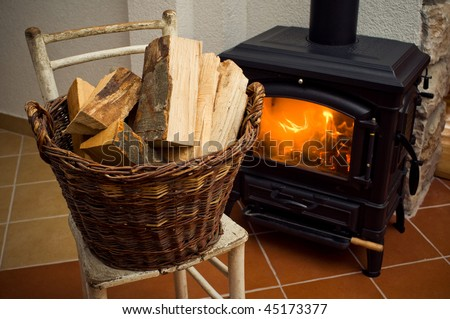 Basket of logs in front a burning fire - stock photo