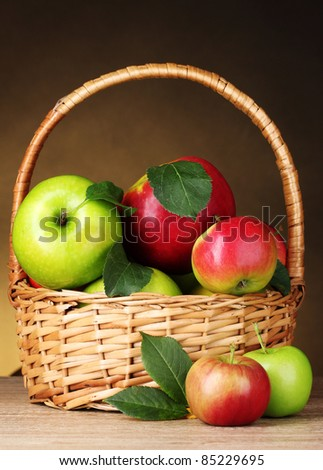 Basket of organic apples on brown background - stock photo