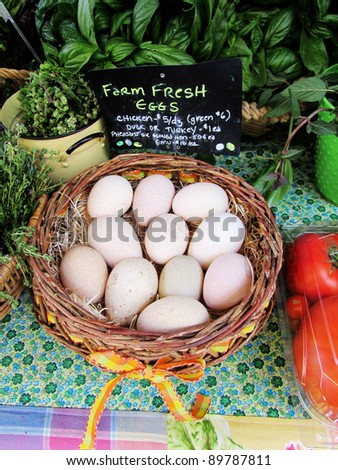 Basket of organic farm eggs, with herbs at an organic farmers market - stock photo