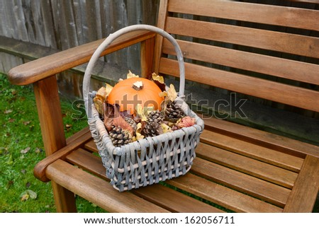 Basket of pumpkin, leaves and pine cones collected in autumn time on a garden bench - stock photo