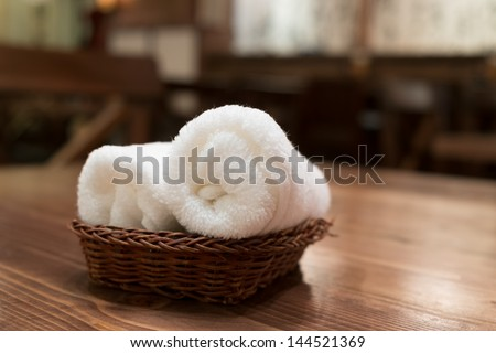 Basket of pure white towels on wooden table in japanese restaurant - stock photo