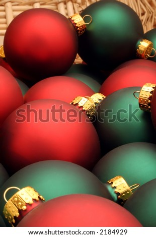Basket of red and green Christmas ornaments decorated with a tartan bow
