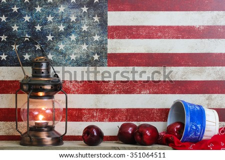 Basket of red apples, bandanna, and antique lantern by vintage American canvas flag  background - stock photo