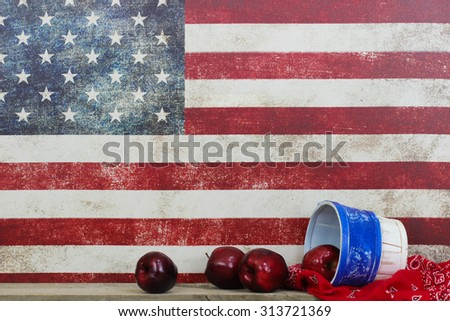 Basket of red apples on red handkerchief by vintage American flag canvas background - stock photo
