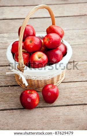 basket of red apples on wood floor aerial view - stock photo