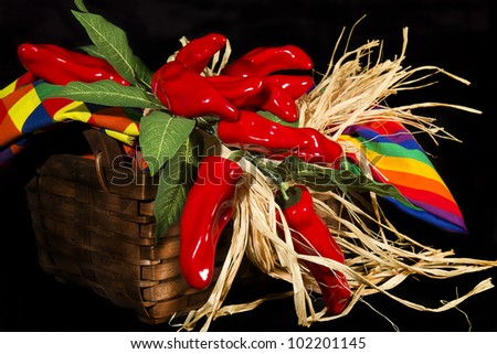 Basket of red hot peppers and festive material on black background