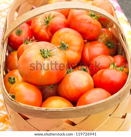 Basket of red ripe tomatoes on display at the market - stock photo