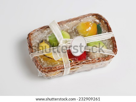 Basket of sweet marzipan almond fruit on withe background. - stock photo