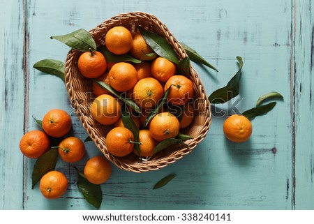 Basket of Tangerines on a wooden table - stock photo