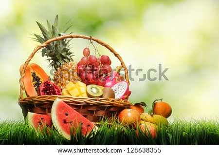Basket of tropical fruits on green grass. - stock photo
