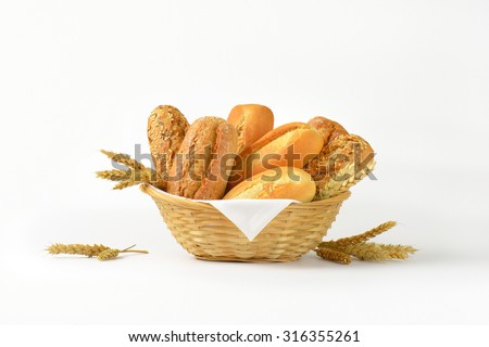 basket of various bread rolls and buns on white background - stock photo