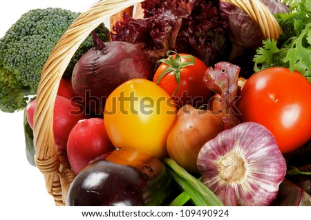 Basket of Various Vegetables with Broccoli, radishes, lettuce, onions, leeks, beets, carrots, red tomatoes, yellow tomatoes, parsley close up