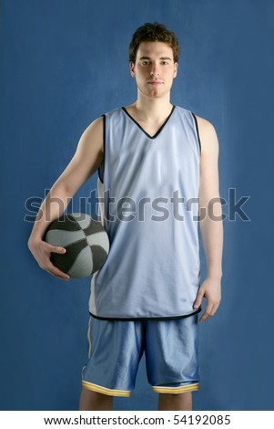 Basket player young man over blue grunge background - stock photo