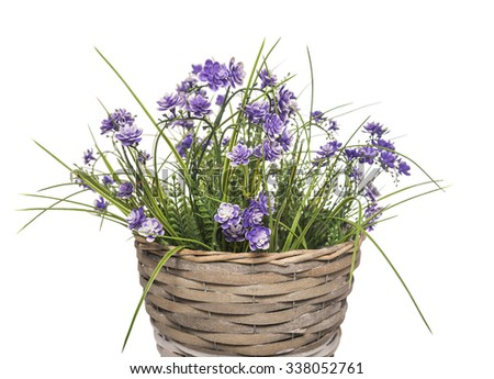 Basket with artificial flowers on a white background.