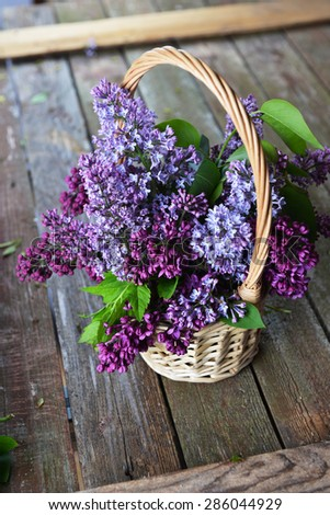 basket with  branch of lilac on wooden background