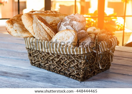 Basket with bread. Bread basket on wooden table. Morning in bakery. Choose your favorite sort. - stock photo