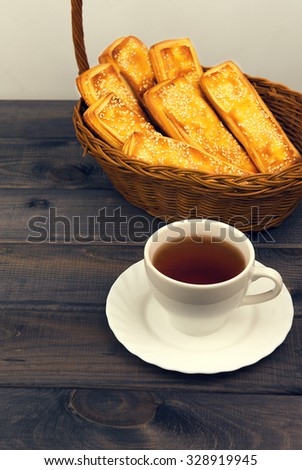 Basket with bread sticks, white porcelain cup standing on a wooden table background - small DoF focus put only to pier