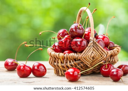 Basket with cherry close up on table in garden - stock photo