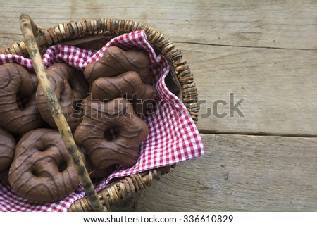Basket with Christmas chocolate gingerbread on rustic old wood with copy space - stock photo