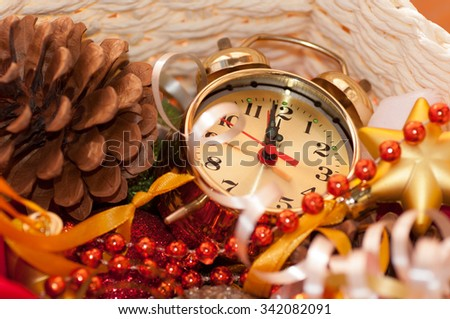 basket with Christmas toys and clock hands for 12 hours - stock photo