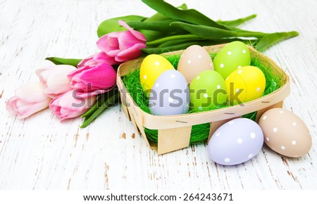 Basket with easter eggs and pink tulips on a old wooden background - stock photo