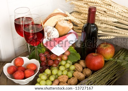 Basket with food and red wine on a barrel