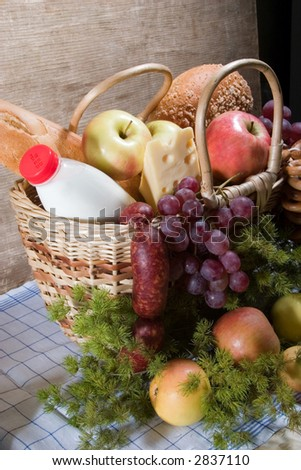 basket with food - apples, cheese, milk, vinegar etc. With wooden wall on the background