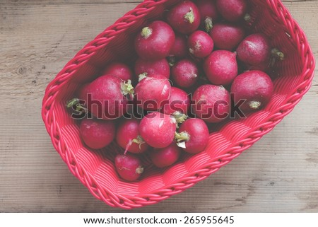 Basket with fresh radish on wooden background, top view. Filtered image. - stock photo