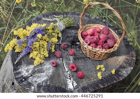Basket with fresh raspberries and flowers.